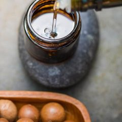 a bottle of macadamia nut oil being poured into a small jar sitting on top of a rock, next to a brown bowl of macadamia nuts