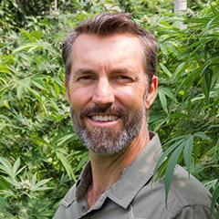 Steve Sakala, CEO and Co-founder of Mana Artisan Botanics standing in front of hemp plants