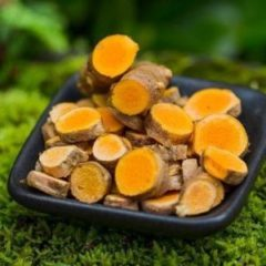 A black bowl of chopped turmeric aka olena sitting in a bed of green moss